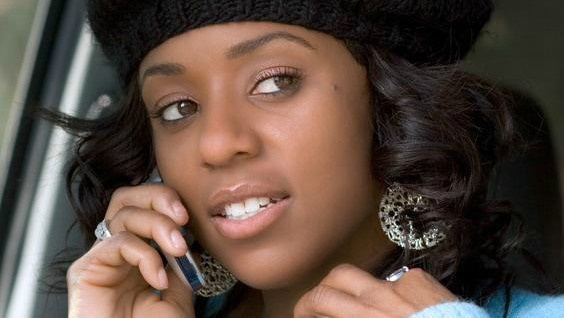 Portrait of Flirty African-American in the car with mobile phone